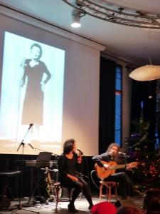 Sur le panneau mural derrière les artistes, des images de Piaf défilent et rendent l'atmosphère dense et prenante